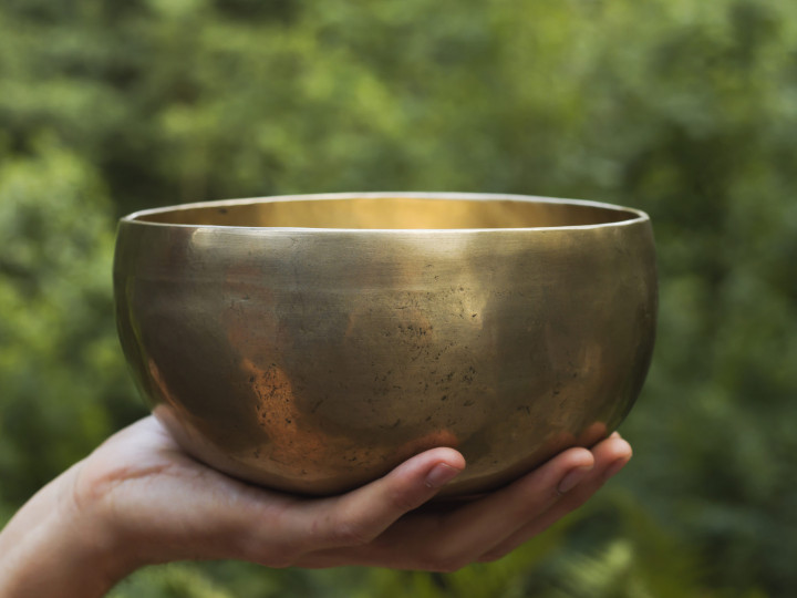 hand holding a tibetan bowl